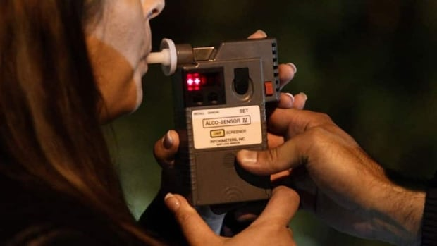 An RCMP officer performs a breathalyzer test on a driver during a roadside check in Surrey, B.C., in 2010. New figures released by Statistics Canada on Thursday show that the number of impaired-driving cases reported by police in 2011 are up from the previous year, and the proportion of female drivers is growing as well.