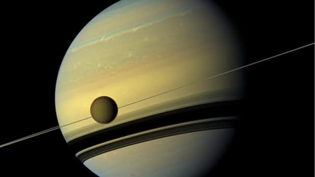 An image by NASA's Cassini spacecraft shows Saturn's largest moon Titan passing in front of the giant planet. Researchers have discovered windblown sand is filling in the moon's craters.