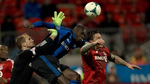 Toronto FC keeper Stefan Frei, left, leaps in as teammate Danny Califf, right, battles with Montreal Impact's Hassoum Camara, centre, for the ball during the second half of Canadian championship Wednesday night at BMO Field.