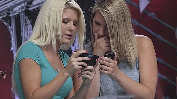 Taylor Johnson, left, of Yorba Linda, Calif., and Rebecca Lessie, of Reading, Penn., inspect their texts during the 2012 LG U.S. National Texting Championship on Aug. 8 in New York. In Canada, the Competition Bureau has filed a lawsuit against Bell, Rogers and Telus over the costs of premium texting services.