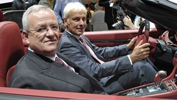 Martin Winterkorn (front), the CEO of both Volkswagen and Porsche Automobil Holding, poses with Porsche CEO Matthias Mueller in a Porsche 911 during the annual general meeting of Porsche Automobil Holding in Stuttgart on June 25.