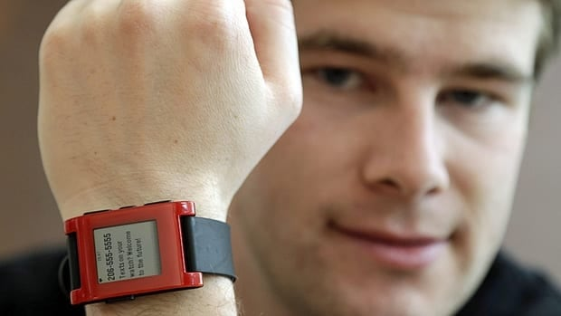 Eric Migicovsky, CEO of Pebble, displays his company's smart watch. The startup, which began shipping the product in January, faces serious competition with big names like Sony and Motorola.