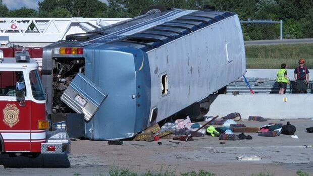 Seat cushions, clothing and other objects line the pavement next to the wreckage of bus that crashed Saturday on Indianapolis' far north side while carrying teenagers returning from a summer camp in Michigan.