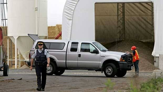 An RCMP officer and an unknown official are seen in front of a tent containing manure at a mushroom farm in Langley, B.C., fter three people were overcome by an unknown substance and died on September 5, 2008.