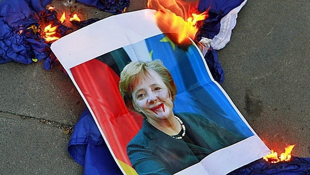A defaced poster of Germany Chancellor Angela Merkel is set alight during an anti-bailout protest in Cyprus earlier this month.