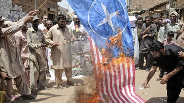 Pakistani protesters burn representations of U.S. and NATO flags during a demonstration to condemn U.S. drone strikes in the tribal areas, in Multan, Pakistan.