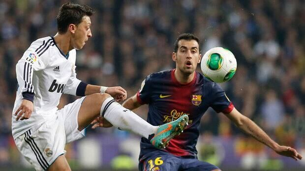 Real Madrid's Mesut Ozil, left, fights for the ball with Barcelona's Sergio Busquets during their Copa del Rey semifinal match Wednesday.