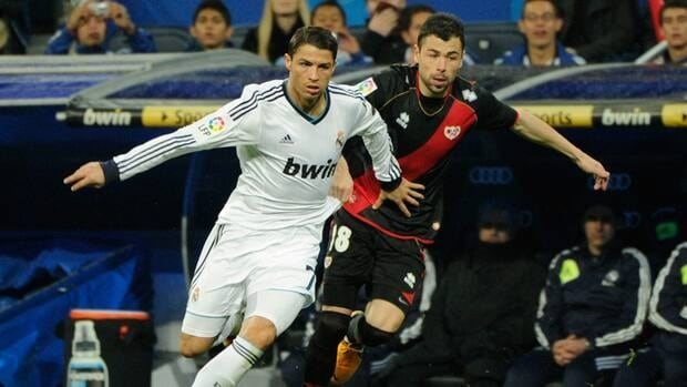 Real Madrid's Cristiano Ronaldo, left, vies with Rayo Vallecano's Javier Fuego at the Santiago Bernabeu stadium in Madrid on February 17, 2013.