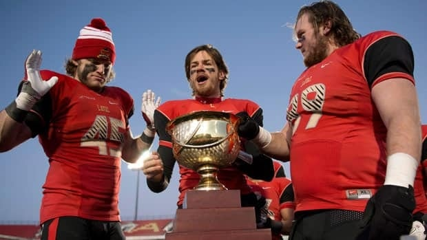 Laval University Rouge et Or quarterback Tristan Grenon, centre, carries the Uteck Bowl trophy as teammates Arnaud Gascon-Nadon and Christophe Normand look on.