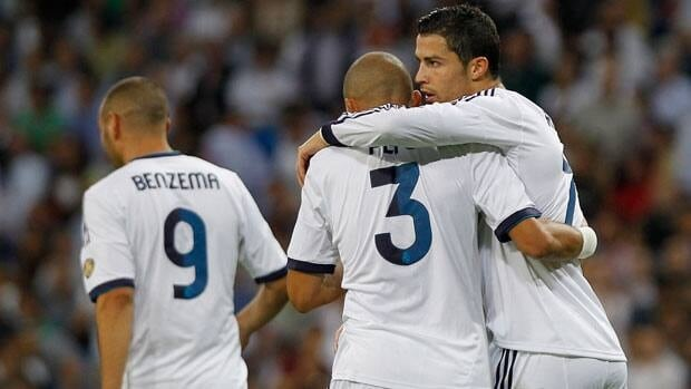 Real Madrid's Cristiano Ronaldo from Portugal, right, hugs teammate Pepe after scoring, with Karim Benzema also on the pitch at the Santiago Bernabeu stadium on Sunday.