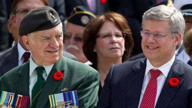 Prime Minister Stephen Harper, right, sits next to a Korean war veteran as he attends a wreath-laying ceremony at the Korea Veterans National Wall of Remembrance in Brampton, Ont., on Wednesday.