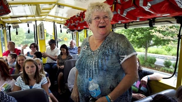 Bus monitor Karen Klein, of Greece, N.Y., is surrounded by school children while riding a tourist duck boat in Boston. The 68-year-old school bus monitor will receive $700,000 from an online fundraising campaign.