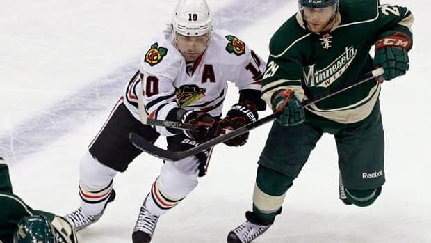 Chicago Blackhawks' Patrick Sharp, left, and Minnesota Wild player Jason Pominville, chase the puck on April 9, 2013