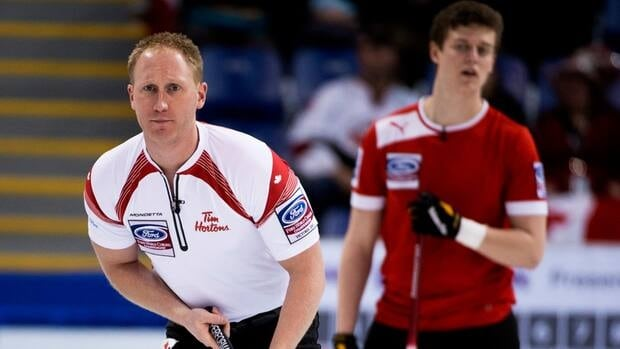 Denmark lead Troels Harry, right, looks on as Canada skip Brad Jacobs watches his shot during an afternoon draw at the world men's curling championship Thursday in Victoria.