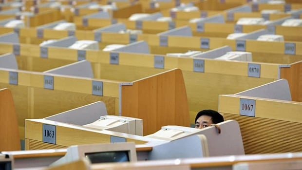 A man looks at rows of empty cubicles in China. A U.S. thinktank says working less could help mitigate the impact of climate change.