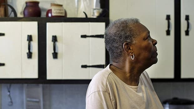 Hattie Watties in front of cabinets that were lowered in her kitchen in Baltimore to allow her easier access to items.