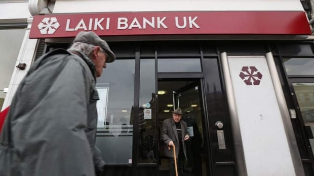 A man walks out of a Laiki (Popular) Bank U.K. branch in northern London on Monday. The people with deposits in the U.K. branches of the bank are protected by U.K. law. Cyprus avoided bankruptcy, and potential turmoil across the eurozone was averted, by securing a last-minute bailout.