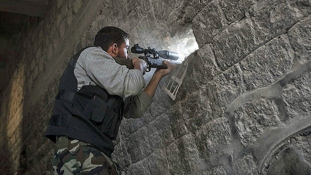 A rebel sniper aims through a hole in the wall that overlooks a position held by Syrian troops  hidden in a nearby building as they attempt to gain ground on the rebel lines during heavy clashes in the Jedida district of Aleppo on Nov. 4.