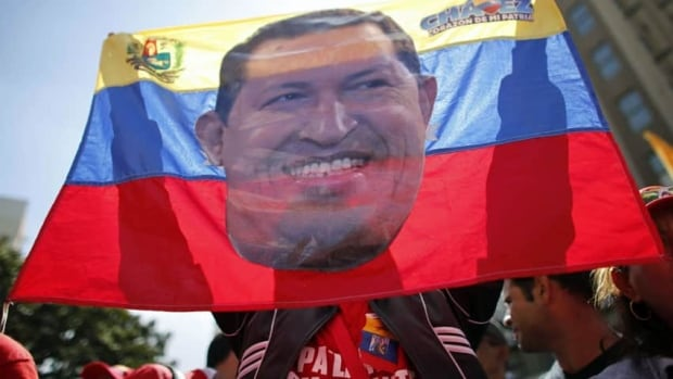 A supporter of Venezuelan President Hugo Chavez waves a flag with a picture of Chavez during a rally in Caracas. Venezuelan Vice-President Nicolas Maduro says he is optimistic that Chavez will recover and return to power after a fourth cancer operation in his pelvic area.