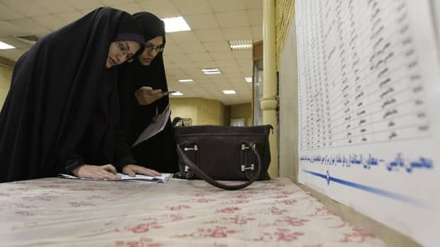 Two Iranian women fill in their ballots for parliamentary elections at a polling station in Tehran, Iran, Friday. Nearly 47,000 polling stations are open to take ballots for Iran's 290-member parliament.