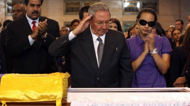 Cuba's President Raul Castro salutes as he stands next to the coffin containing the remains of Venezuela's late President Hugo Chavez, in Caracas, Venezuela, March 7.  At right is Chavez's daughter Rosa Virginia Chavez and left is then Vice-President Nicolas Maduro. Miraflores Press Office/Associated Press