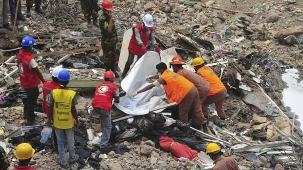 Rescue workers cover the remains of a garment worker retrieved from the rubble of the collapsed Rana Plaza building outside Dhaka on May 2.