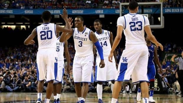 Terrence Jones, centre, and Doron Lamb, left, of the Kentucky Wildcats celebrate in the second half along with their teammates against the Kansas Jayhawks on Monday night.