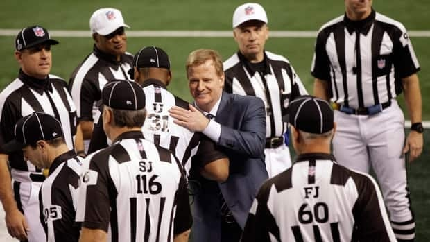 In this file photo from Feb. 6, 2011, NFL commissioner Roger Goodell greets game officials before Super Bowl XLV in Arlington, Texas.