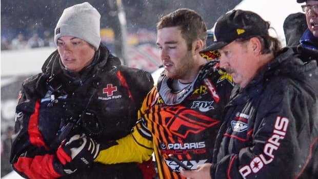 In this photo taken Jan. 24, 2013, Caleb Moore, centre, is helped off the snow following his crash during the ESPN Winter X Games snowmobile freestyle competition in Aspen, Colo. Moore died a week later after suffering complications from injuries suffered during the crash. He was 25.