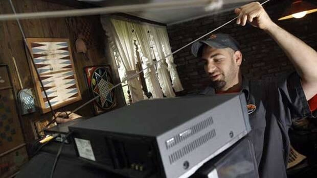 A TV viewer adjusts his old antenna to work with a new digital converter box. Analog signals were phased out in Canada on Tuesday.