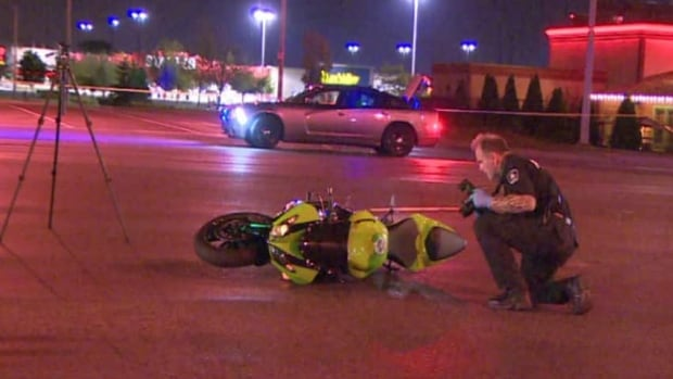 A Halton Regional police officer photographs a motorcycle after a deadly collision in Burlington, Ont., on Thursday night.