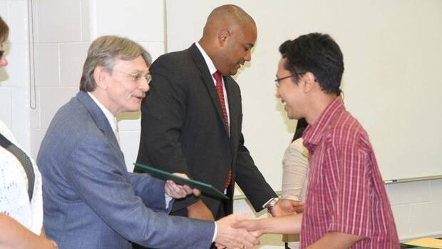 NDP MP David Christopherson awards Iqbal Setiadi with his diploma