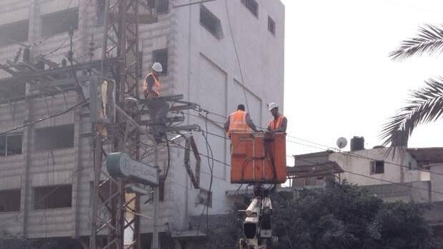 Crews work to restore power in Gaza City on Wednesday after an Israeli airstrike downed lines overnight.
