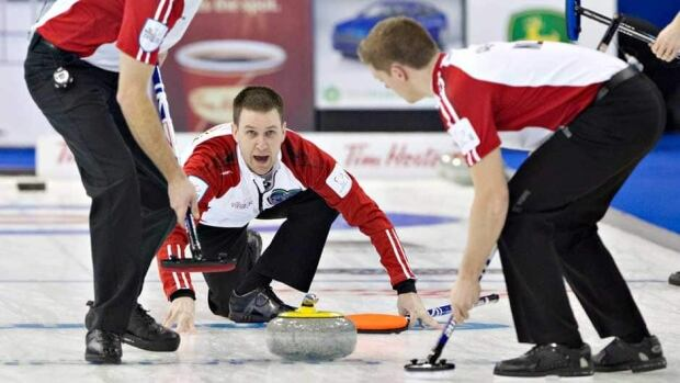 Newfoundland/Labrador skip Brad Gushue calls for the sweep as Adam Casey sweeps during the first draw at the Brier in Edmonton, Alta., on Saturday.