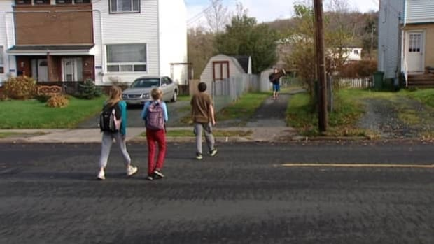 Children cross the street at a site that used to have a crosswalk in Dartmouth.