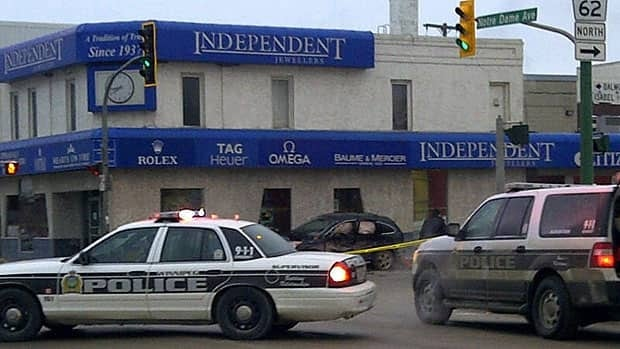 Winnipeg police investigate at the scene of a crash on Notre Dame Avenue Friday.