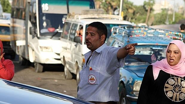 Gas station staff in Cairo try to contain a lineup of drivers waiting for cheap diesel subsidized by the state. Lineups can last four hours on a typical day.