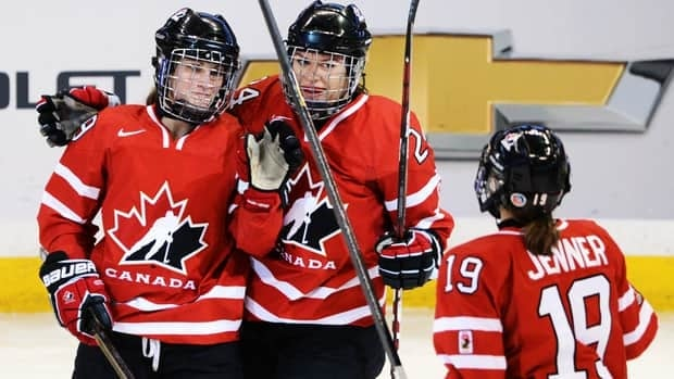 Canada's Marie-Philip Poulin, left, celebrates her first period goal with teammates Natalie Spooner, centre, and Brianne Jenner against Switzerland on Wednesday.