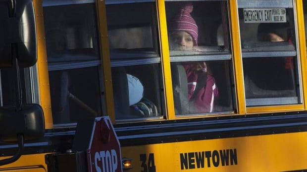 Children from Sandy Hook Elementary School are seen on a school bus making their way to their new school in Monroe as they leave Newtown, Conn. on Thursday. The children are heading back to classes for the first time since a gunman killed 20 of their schoolmates and six staff members.