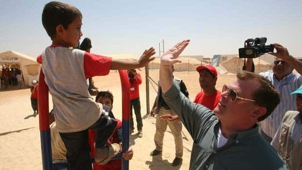Canadian Foreign Affairs Minister John Baird greets a Syrian refugee boy at Zaatari refugee camp, in Mafraq, Jordan, Aug. 11.