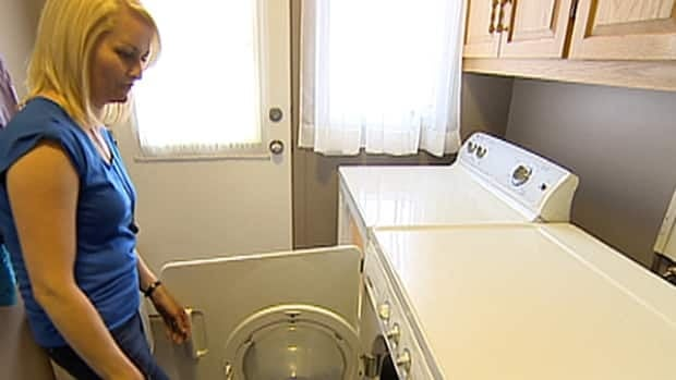 Charlene Onisko does the laundry with the family's new dryer after the previous one caught fire.