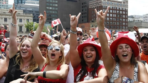 Spectators cheer during Canada Day celebrations on Parliament Hill in Ottawa on July 1, 2012.