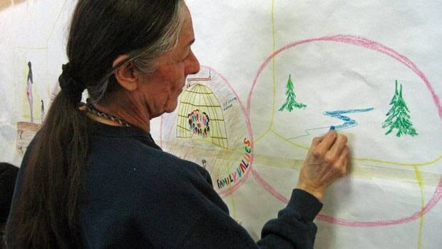Elder Ellen Bruce draws on a mural at the Nishnawbe Aski Nation women's council conference in Thunder Bay.