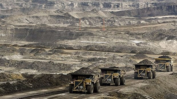 Mining trucks carry loads of oil-laden sand at a project in Ft. McMurray, Alta. A report by the oil industry found that per-barrel carbon emissions from the oil sands rose in 2010 after years of declines.