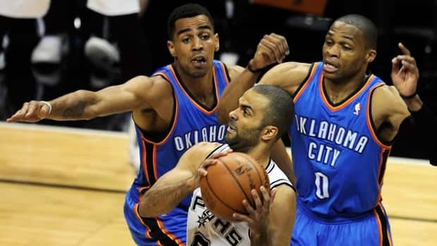 San Antonio Spurs point guard Tony Parker (9), drives to the basket as Oklahoma City Thunder's Thabo Sefolosha, left, and Russell Westbrook (0) defend during the first quarter on Sunday in San Antonio.