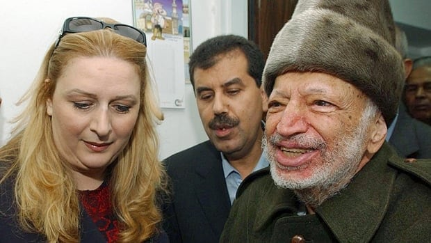 Palestinian leader Yasser Arafat and his wife Suha hold hands prior to Arafat's departure from his compound in the West Bank town of Ramallah, in this Oct. 29, 2004, file photo.