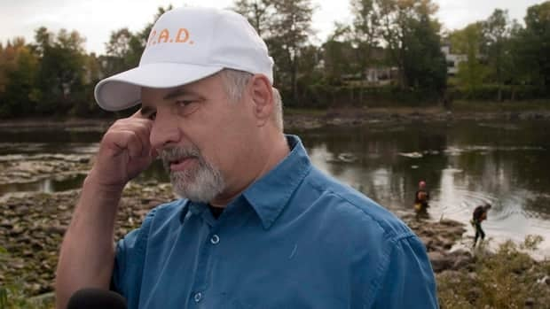 Michel Surprenant, seen here last September as police launched a new search of the river, said he didn't know about his neighbour's past until after his daughter's disappearance.