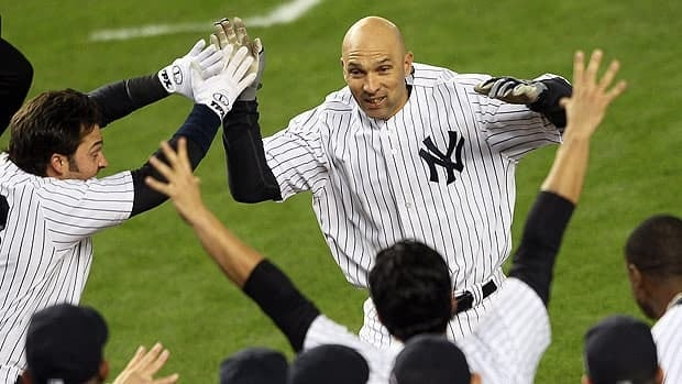 Raul Ibanez is greeted at home plate by jubilant New York teammates after his second home run of the game in the 12th.