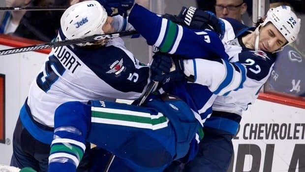 Winnipeg Jets' Mark Stuart, left, and Chris Thorburn, right, rough up Vancouver Canucks' Ryan Kesler during the second period of Thursday's all-Canadian matchup in Vancouver.