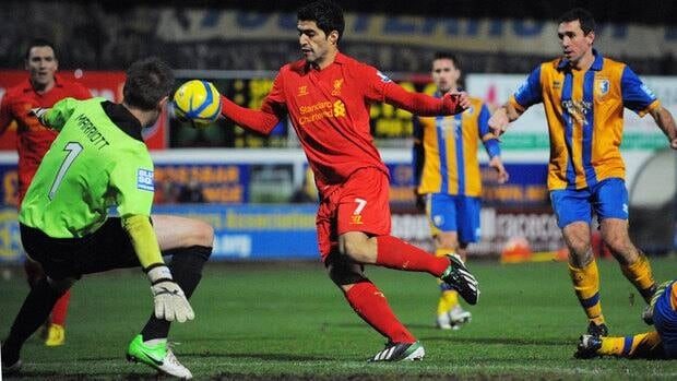 Liverpool forward Luis Suarez, centre, appears to handle the ball in the lead up to his goal against Mansfield on Sunday.